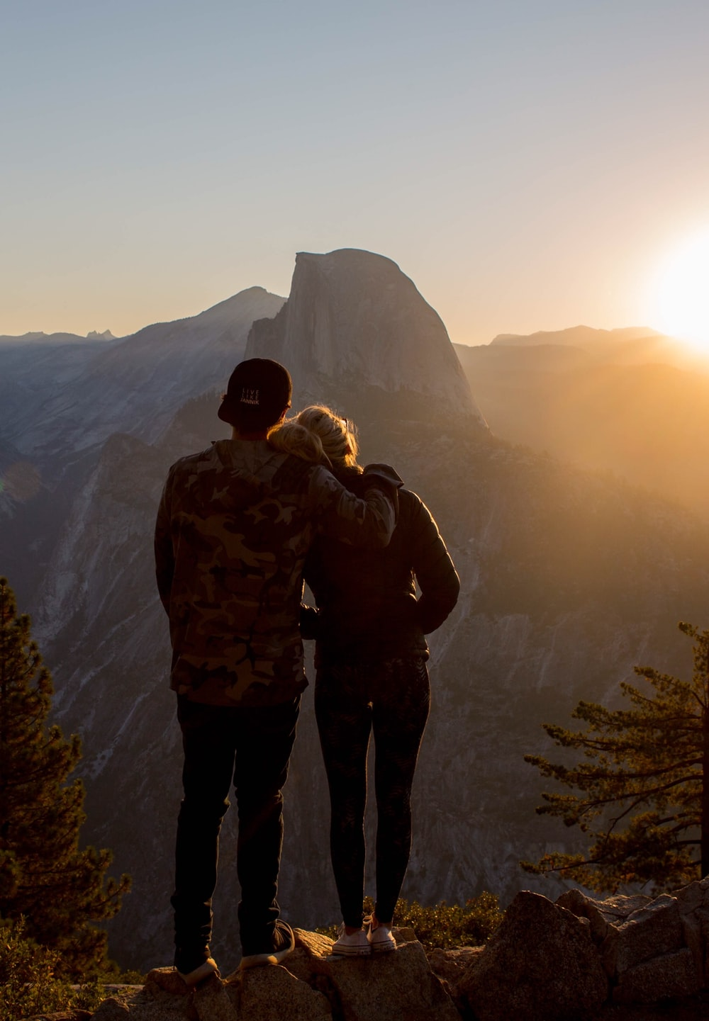 man and woman standing on ridge of hill watching setting sun