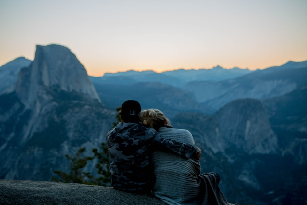 couple sitting by top of rock facing mountain during golden hour