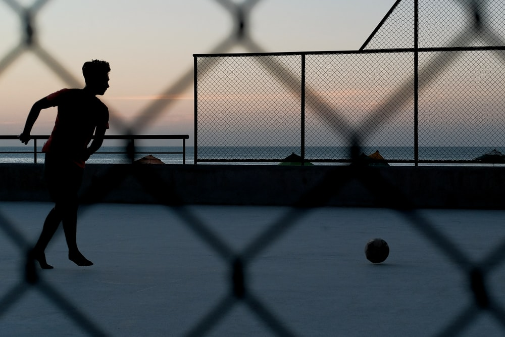 silhouette of person by ball near sea during golden hour