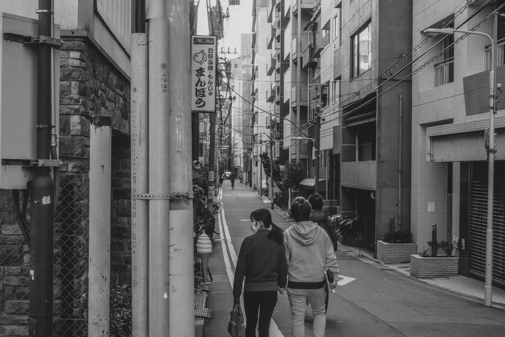 grayscale photo of man and woman holding hands while walking