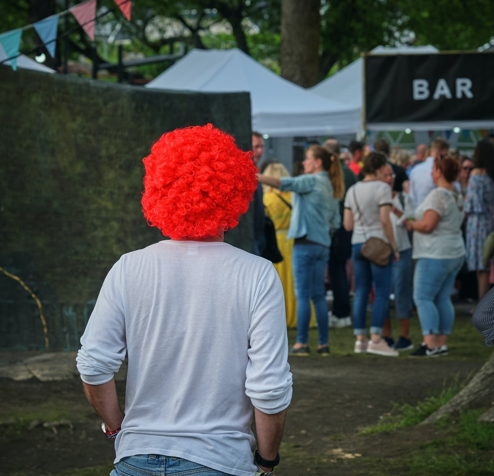 man in white sweat shirt with red wig walking towards bar