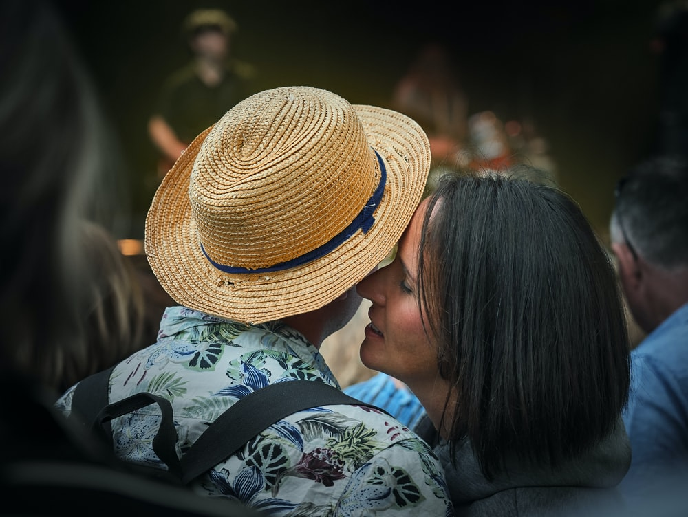 woman whispering on man's right ear with fedora hat