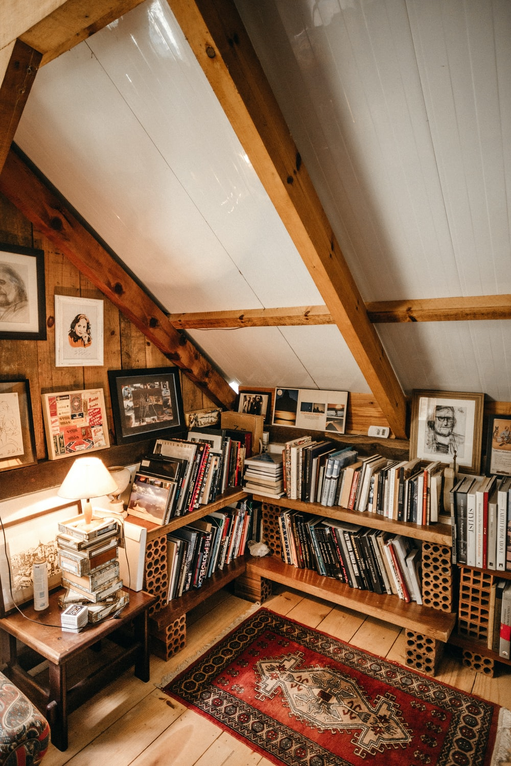books in bookcase by turned-on table lamp