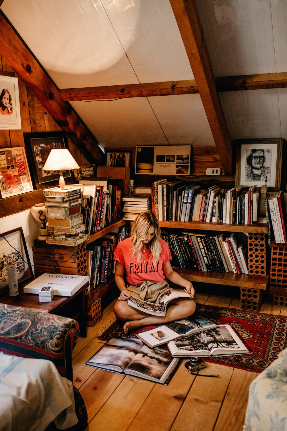 woman sitting on floor reading book in front of book case
