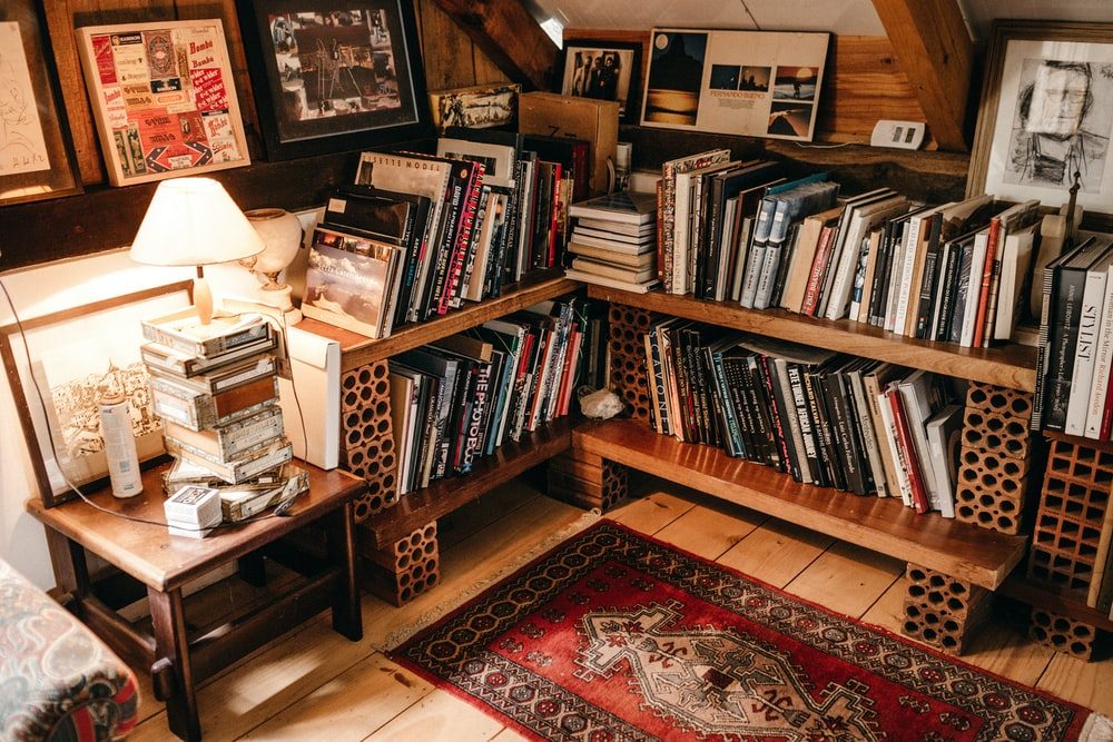 assorted books in shelf near lighted table lamp