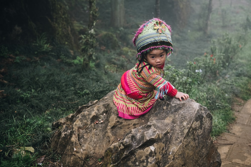 girl in multicolored tribal dress sitting on brown rock