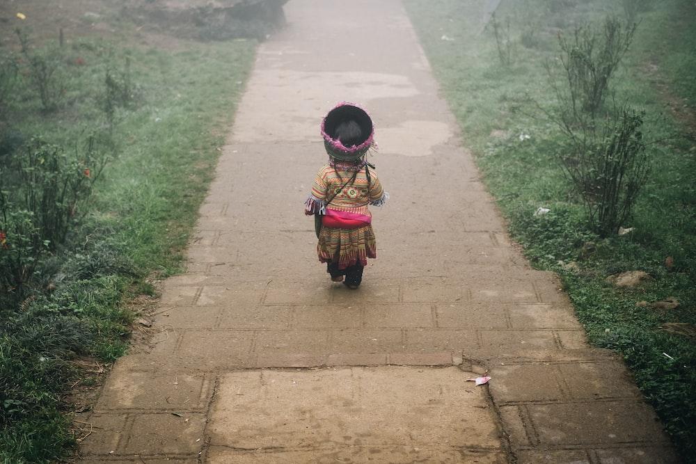 child walking on concrete pathway near green field