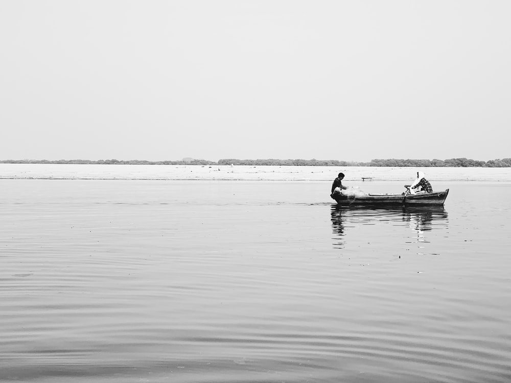 grayscale photography of two people on boat on body of water
