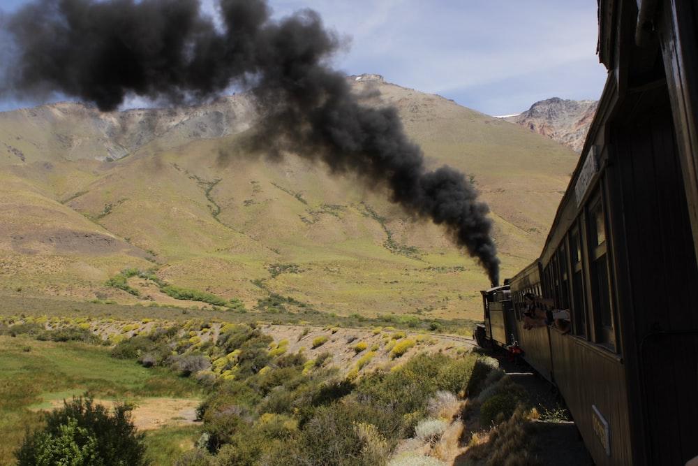 black train near green field and mountain