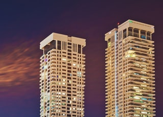 two white high-rise buildings at night time