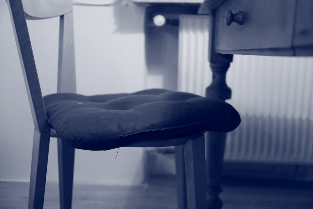wooden chair with tufted pillow cushion by the desk
