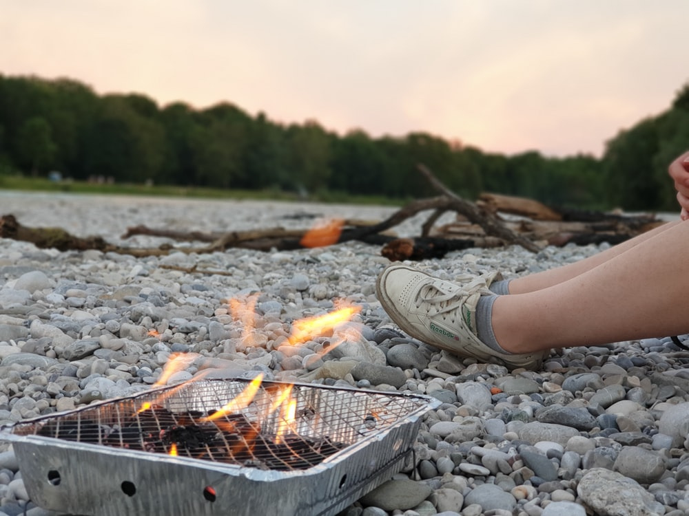 person sitting beside lighted coals in grey grill