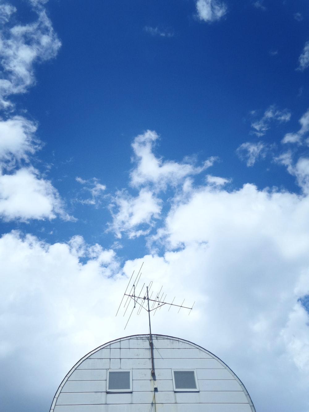 grey antenna on top of white house