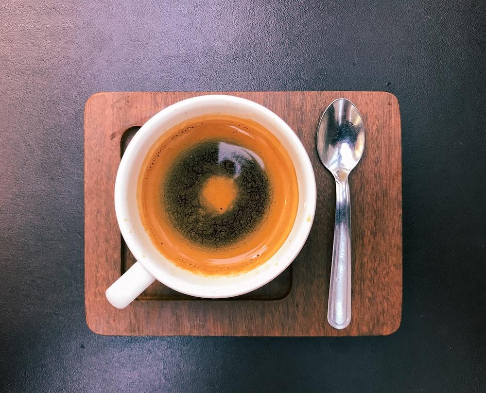 white ceramic teacup beside spoon