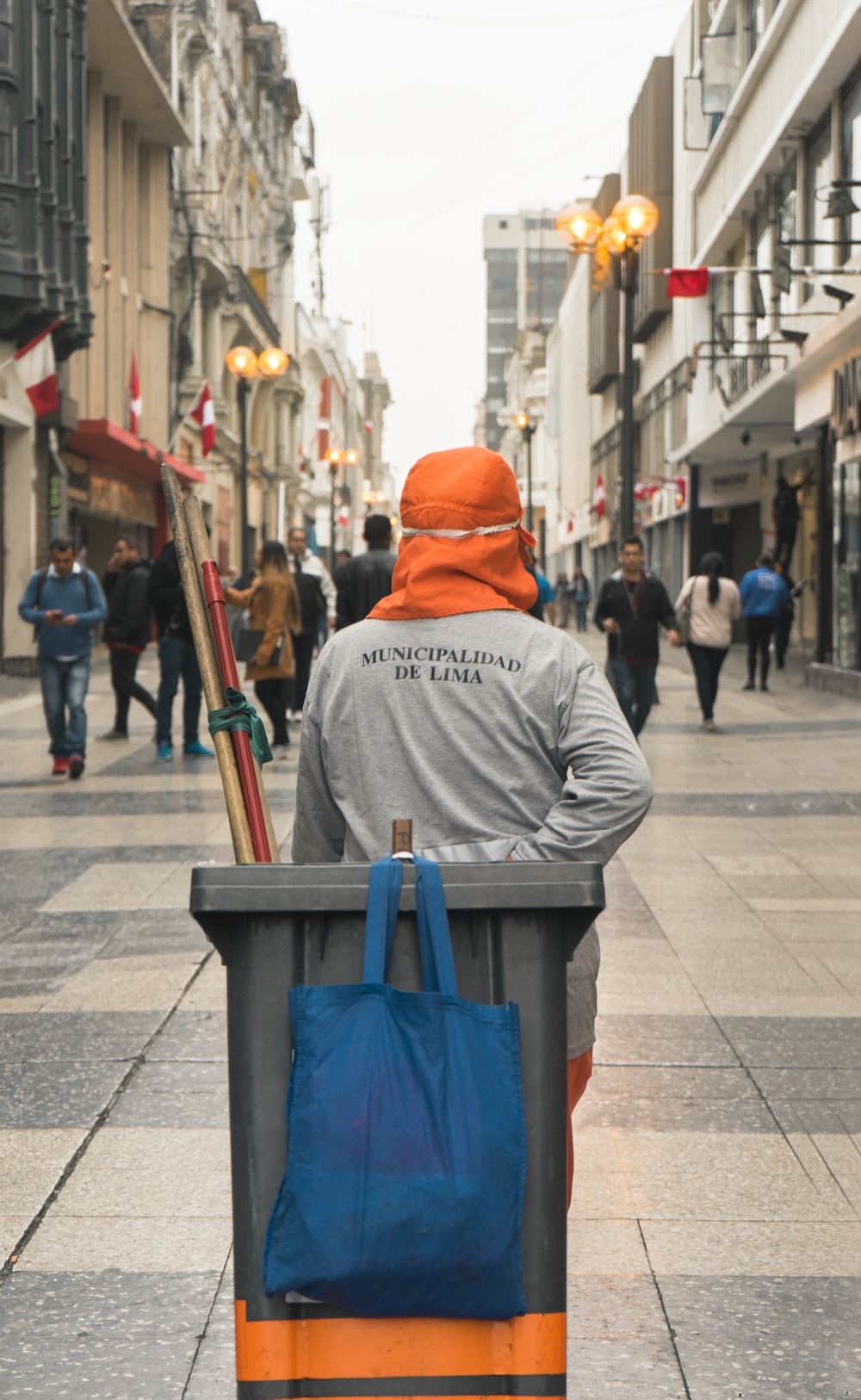 man in grey sweater pulling grey garbage bin