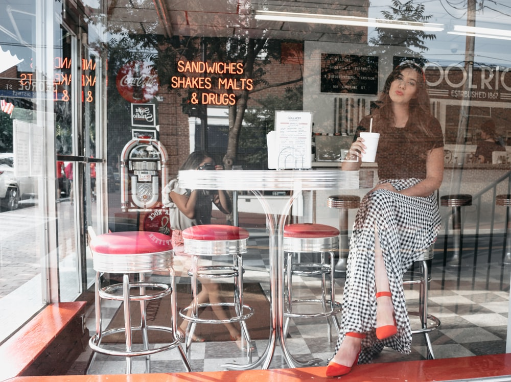 woman sitting on bar stool inside sandwiches shakes malts and drugs