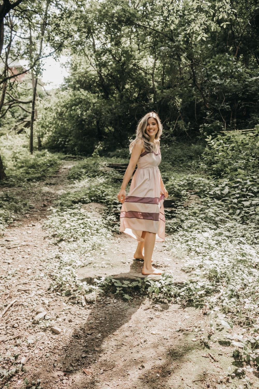 woman in beige walking in the woods