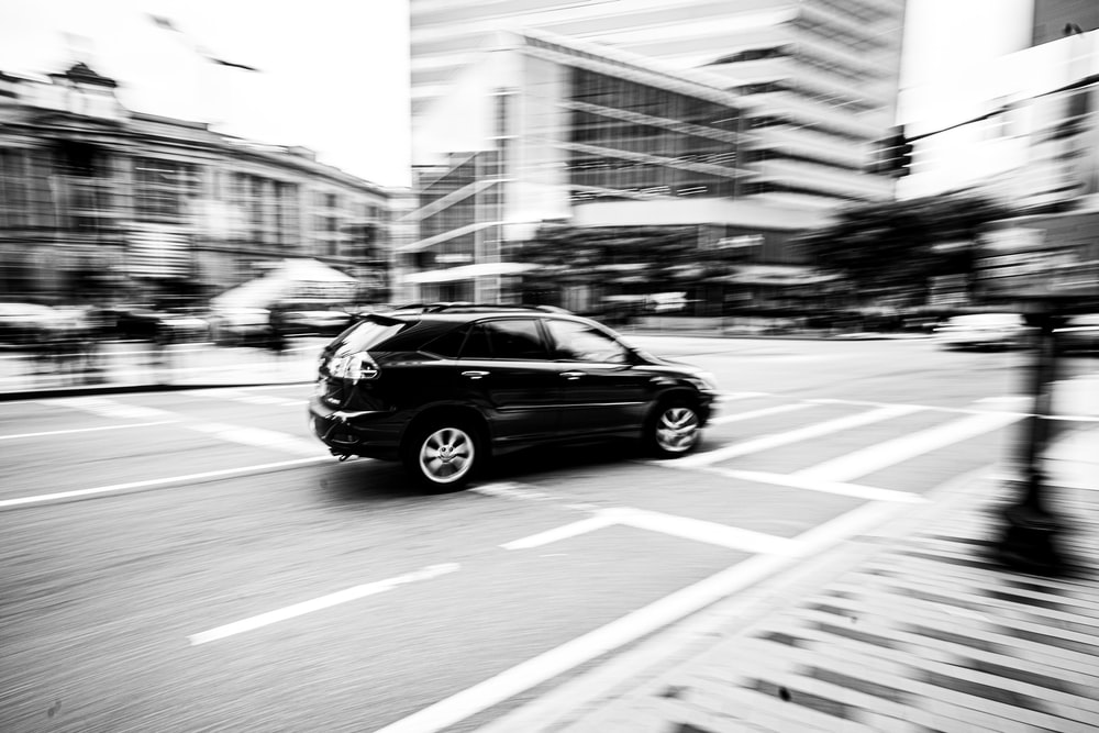 grayscale photography of SUV on road