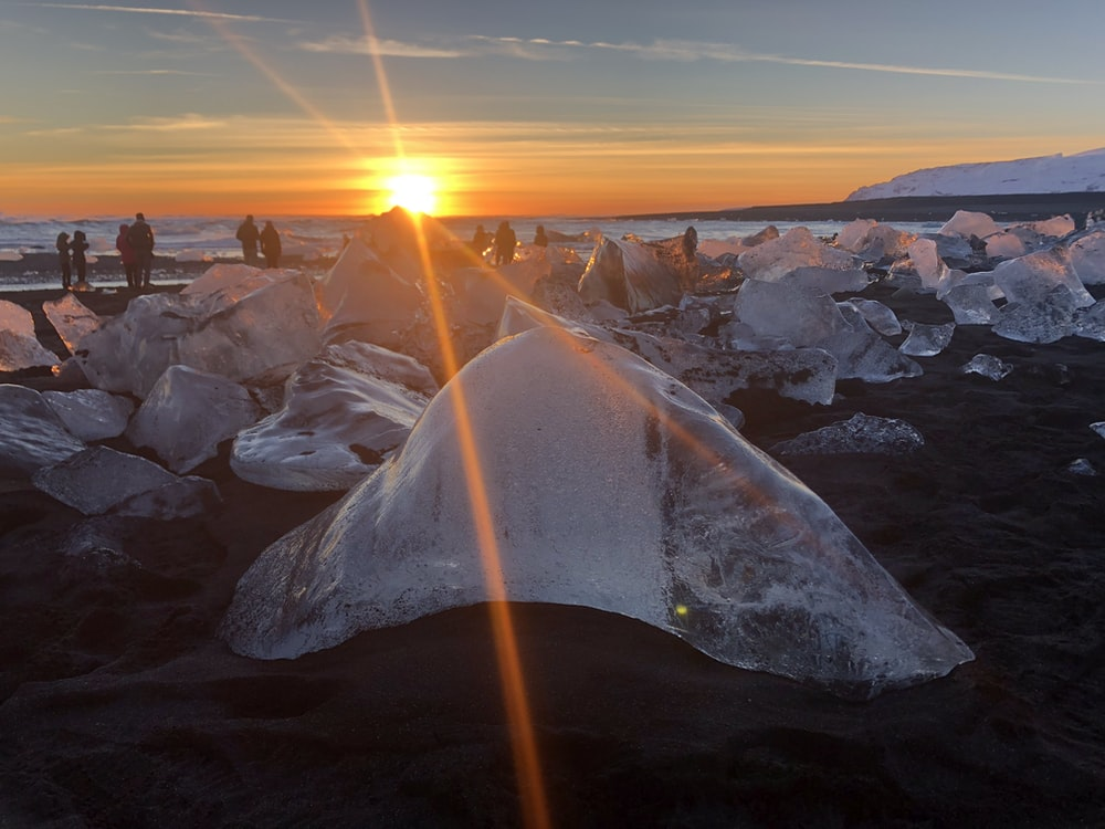 brick of ice on shore during golden hour