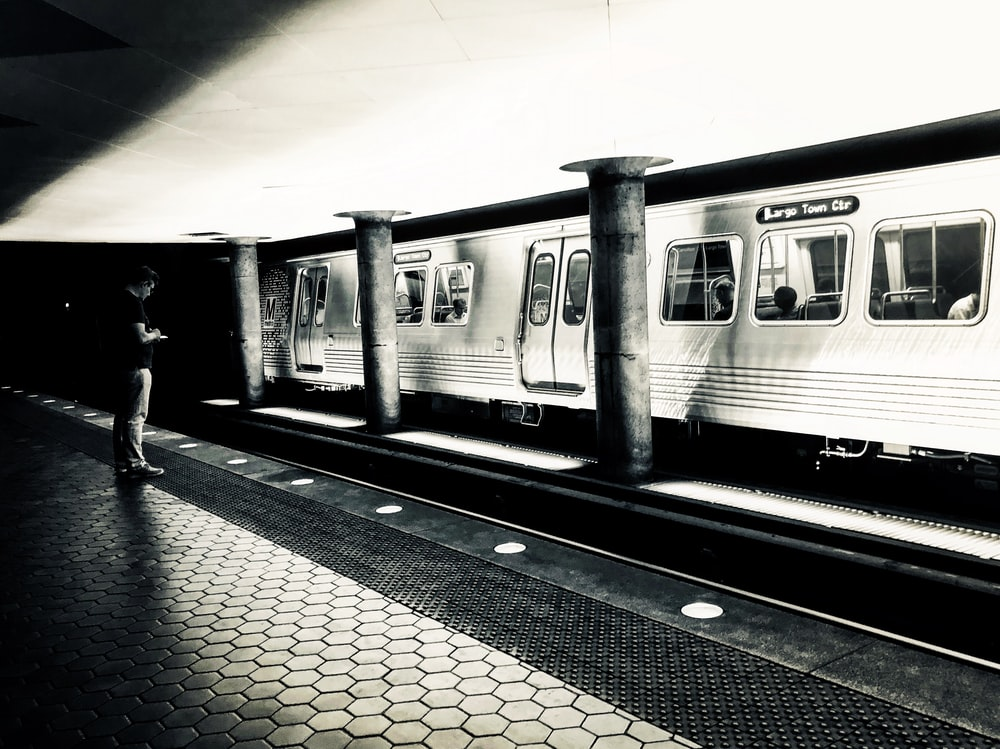 grayscale photo of a train station platform