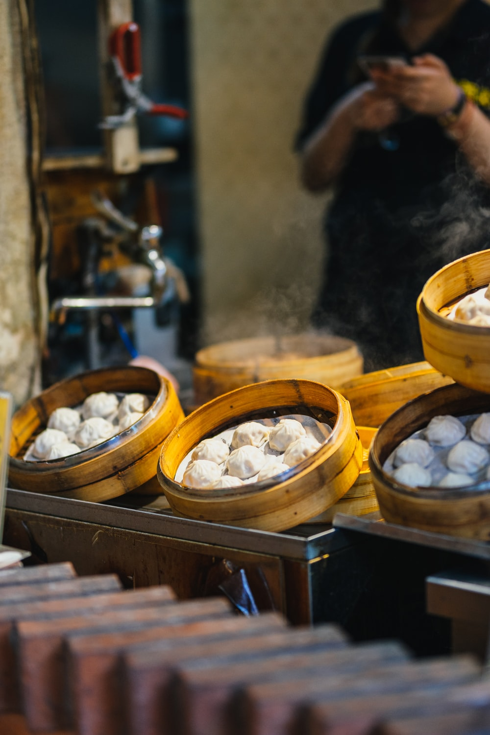 selective focus photography of bamboo steamer with pastry
