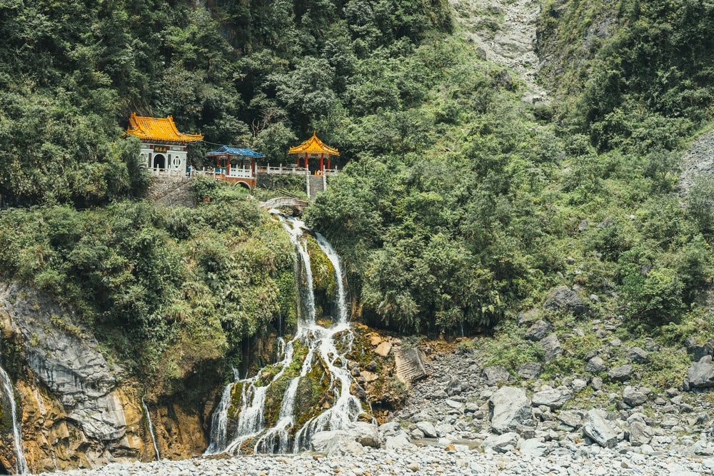 gray, yellow and blue temple by a mountainside and waterfall