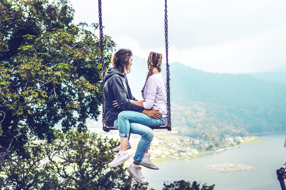 man and woman siting on swing
