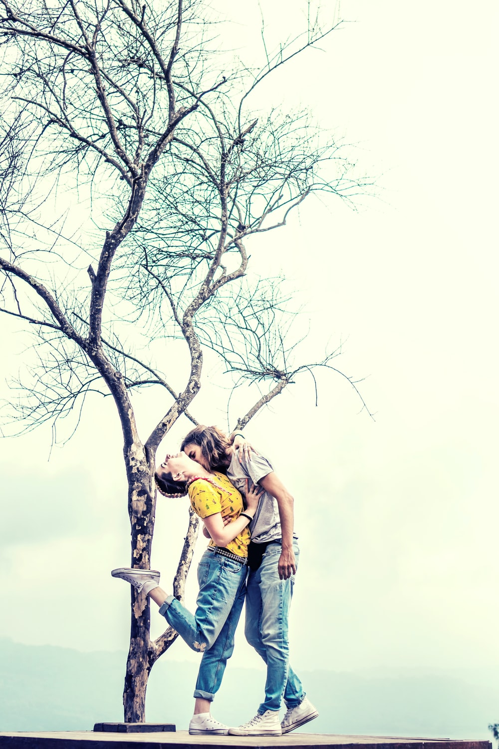 man and woman kissing under leafless tree