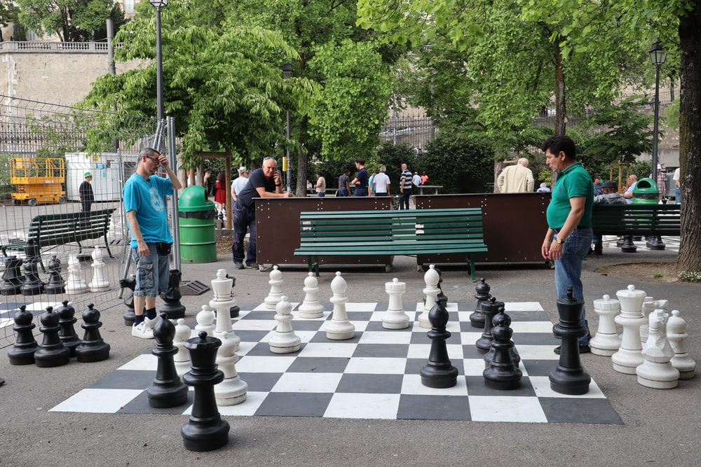 two men playing large chess pieces