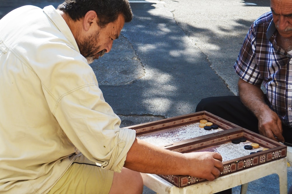 two playing board game at street