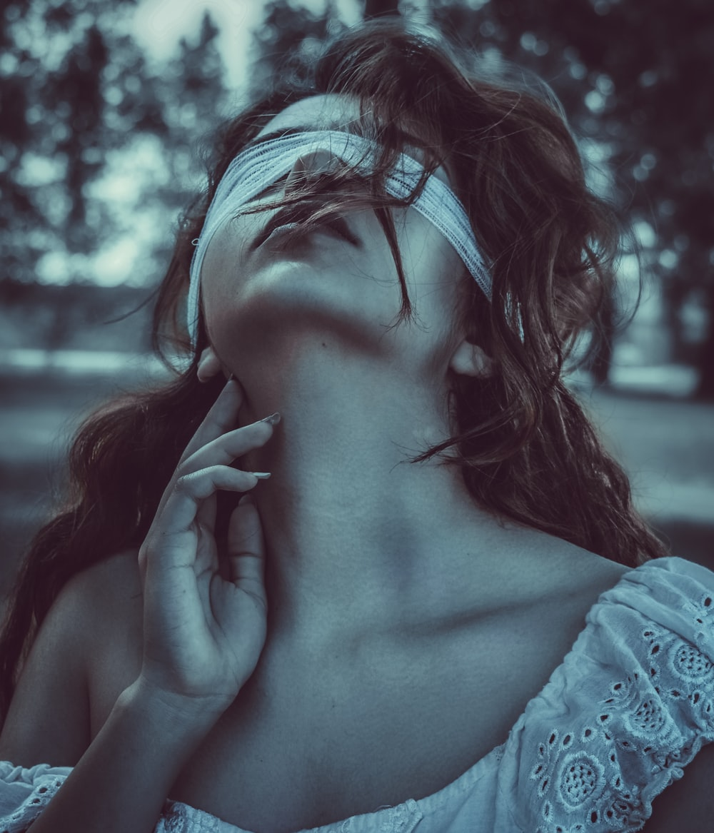 woman with blindfold touching her neck