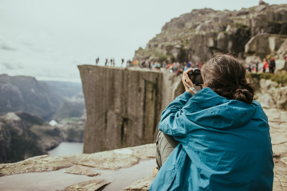 woman in blue jacket taking photo of people on top of cliff with DSLR camera