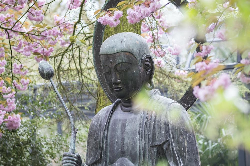 deity statue near tree