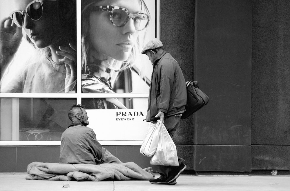 grayscale photo of man with shop bags walking past beggar siting on sidewalk
