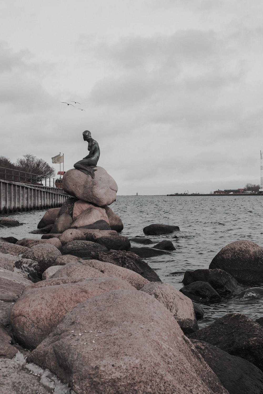 human sitting on rock statue