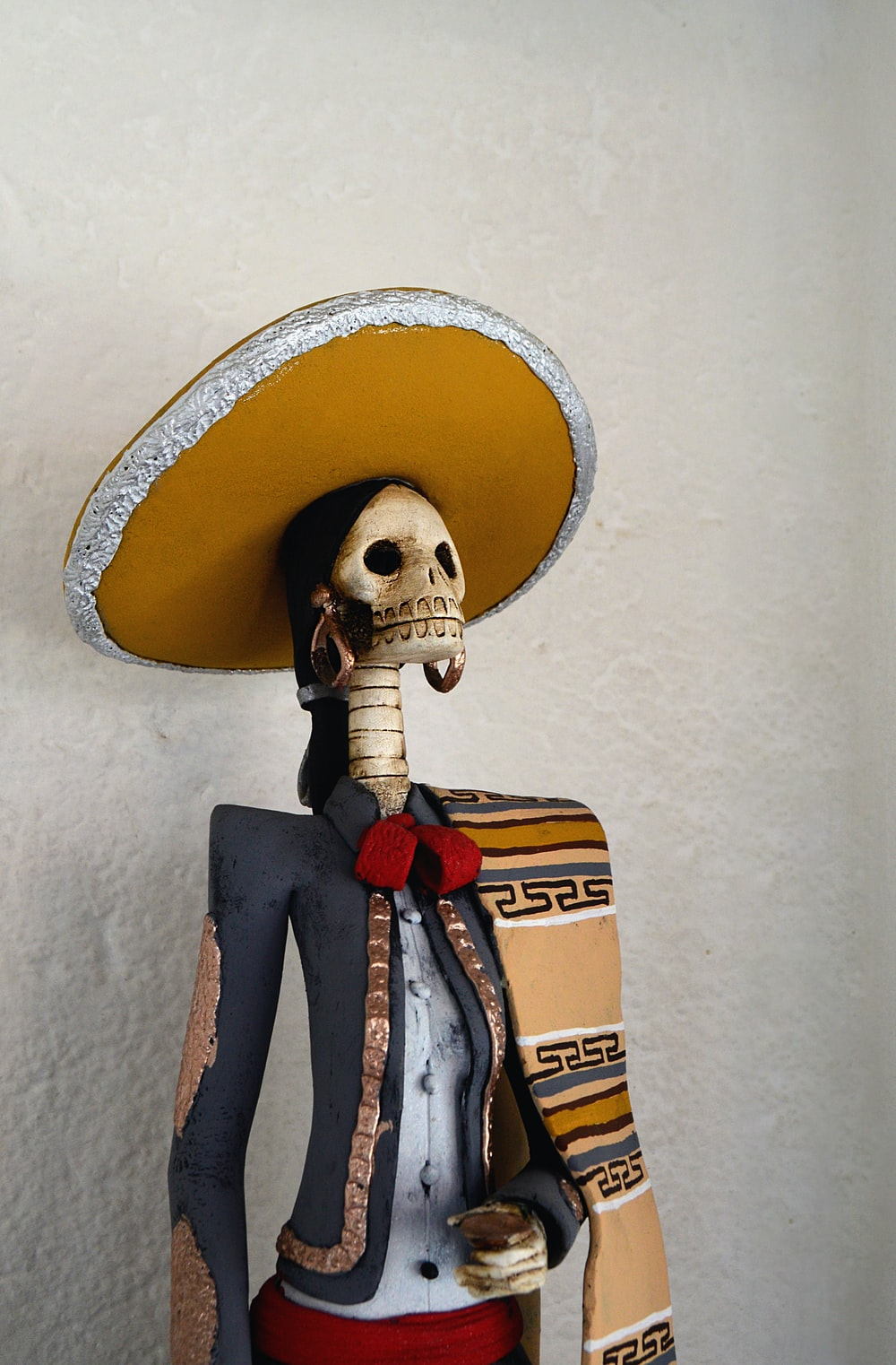 Day of the Dead statue near white painted wall