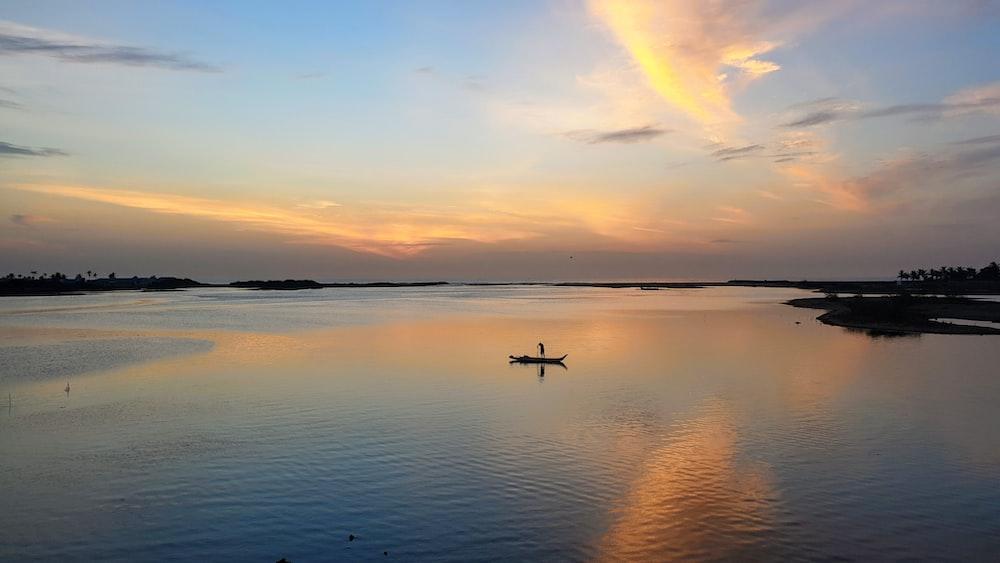 man in boat in under orange sky at sunset