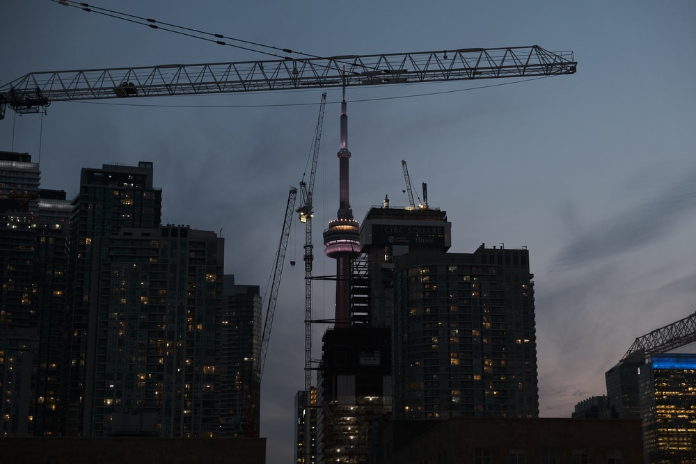 high-rise buildings with crane during nighttime