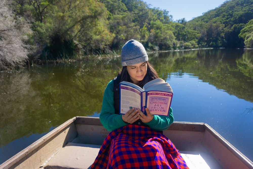 woman sitting on boat while reading book during daytime