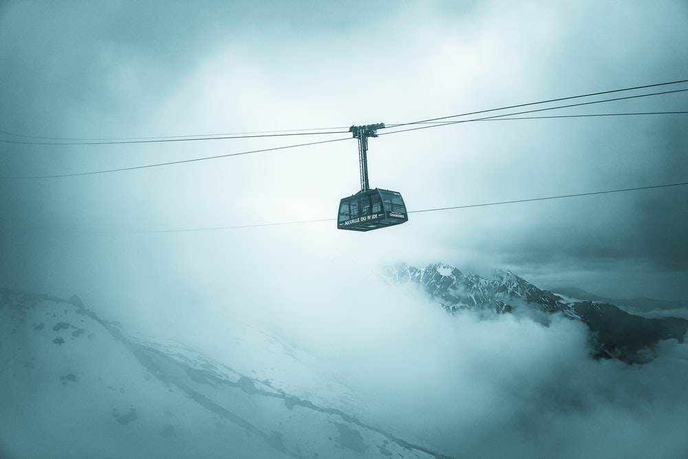 grey cable car traveling above snow covered mountain