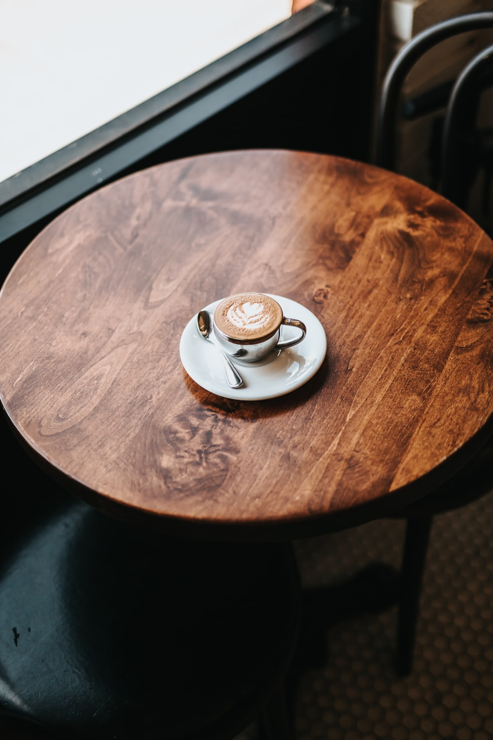 latte in cup on round brown wooden table