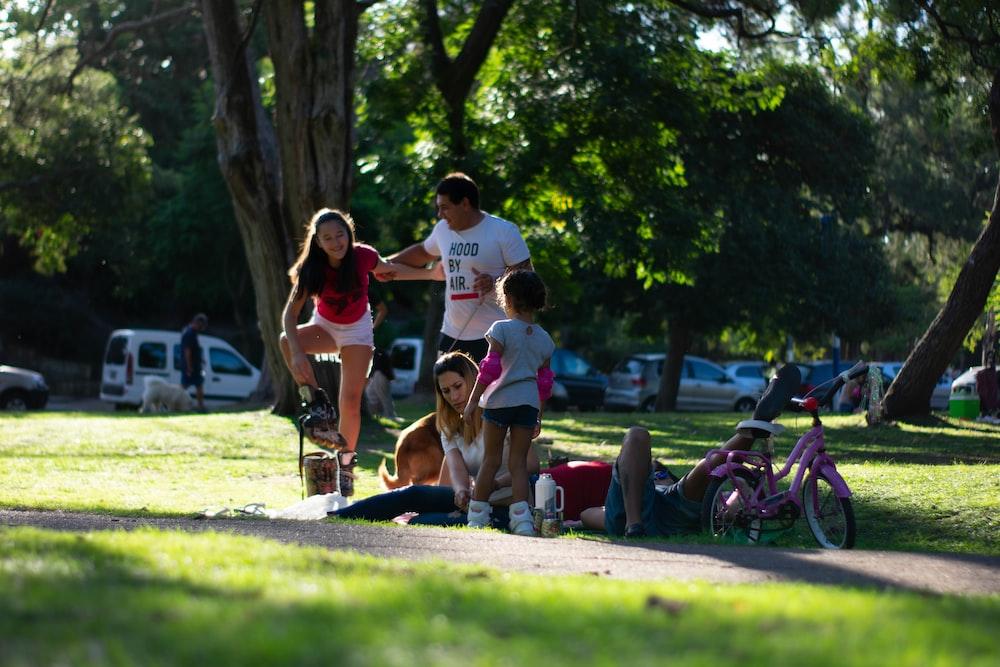 people sitting on grassland during daytime