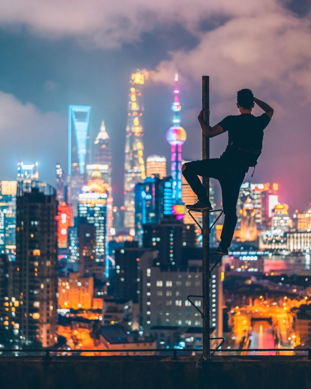 man climbing on rooftop post