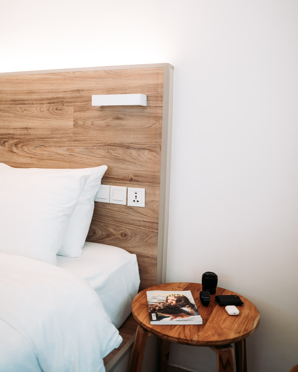 brown wooden headboard and round brown wooden end table