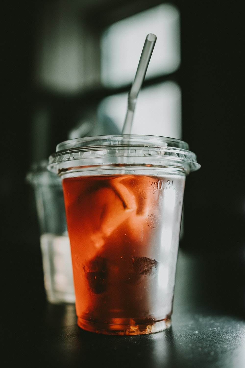 selective focus photo of clear disposable cup with red liquid