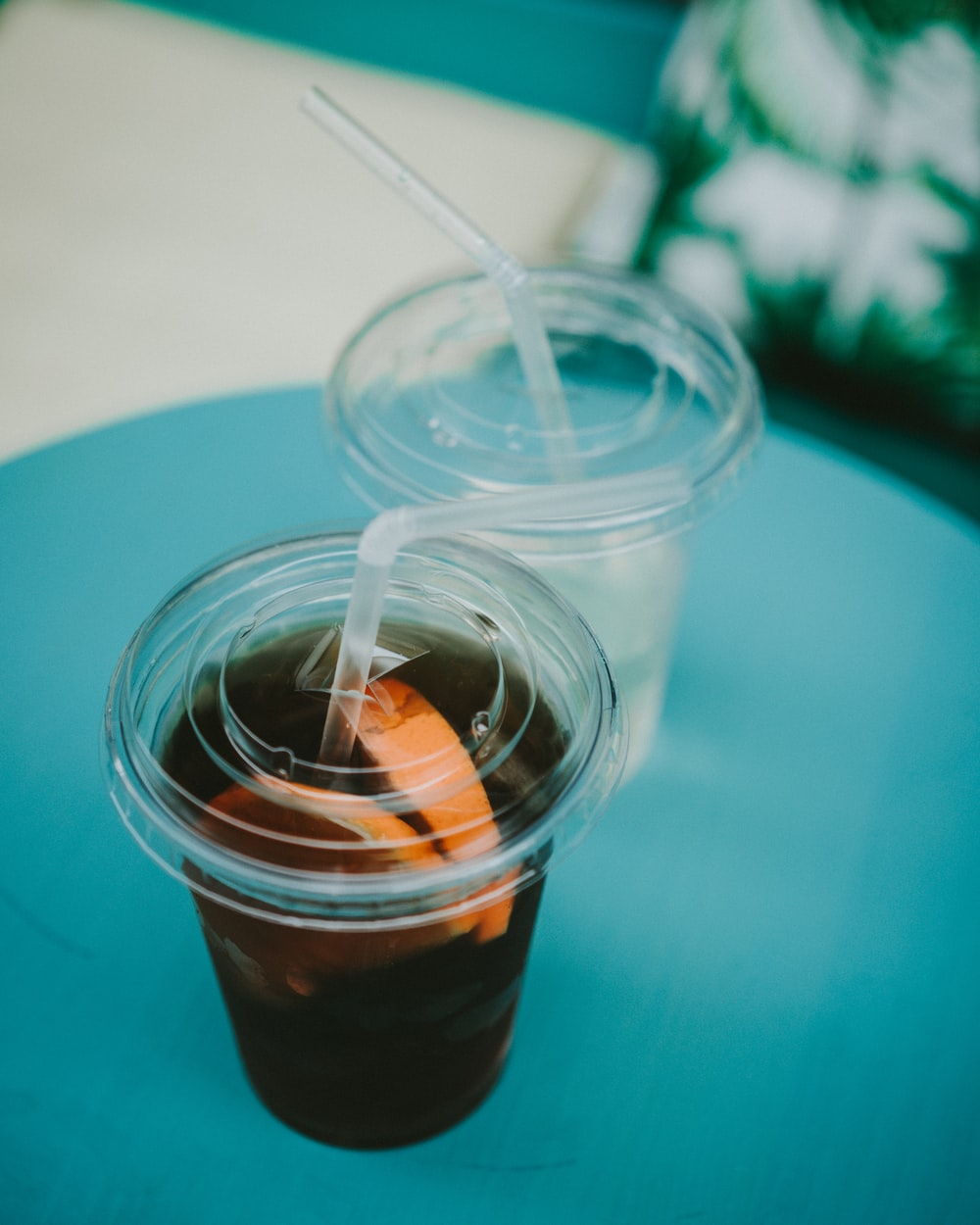 two clear plastic disposable cup with black liquid