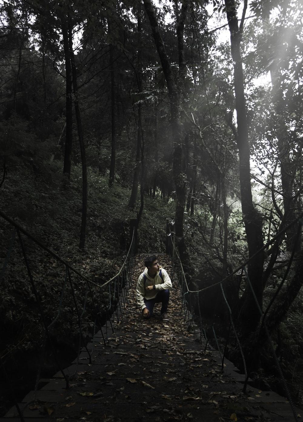 man wearing white dress shirt sitting on brown suspension bridge