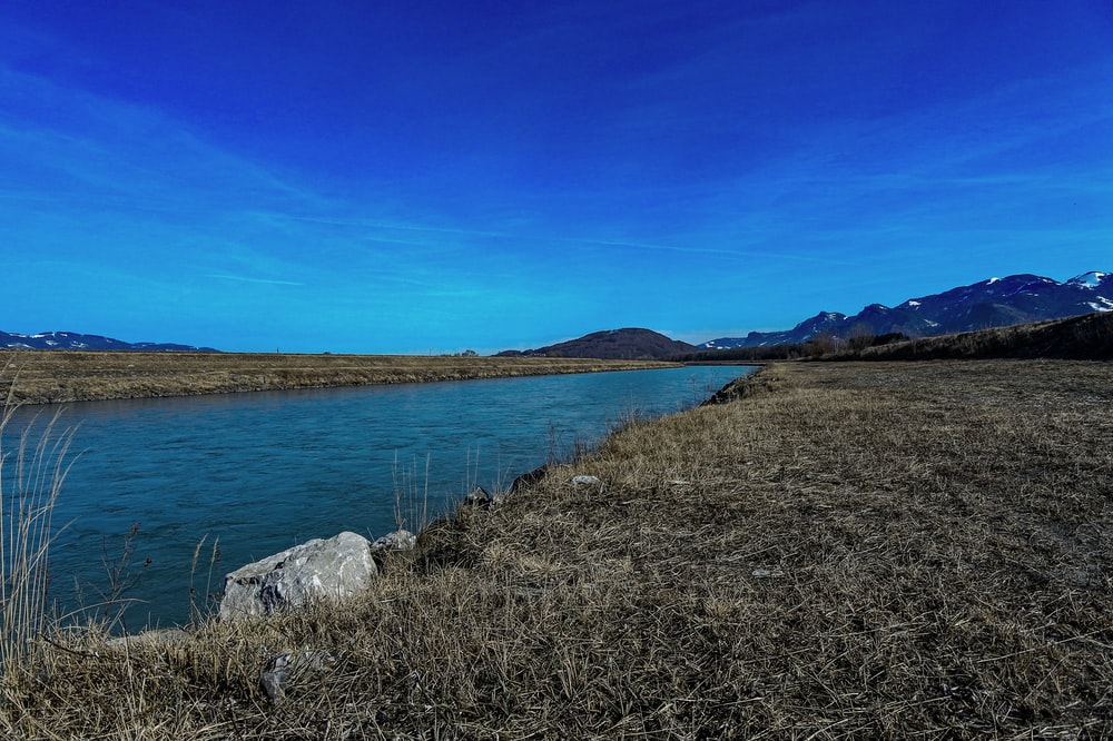 body of water in land under blue sky during daytime