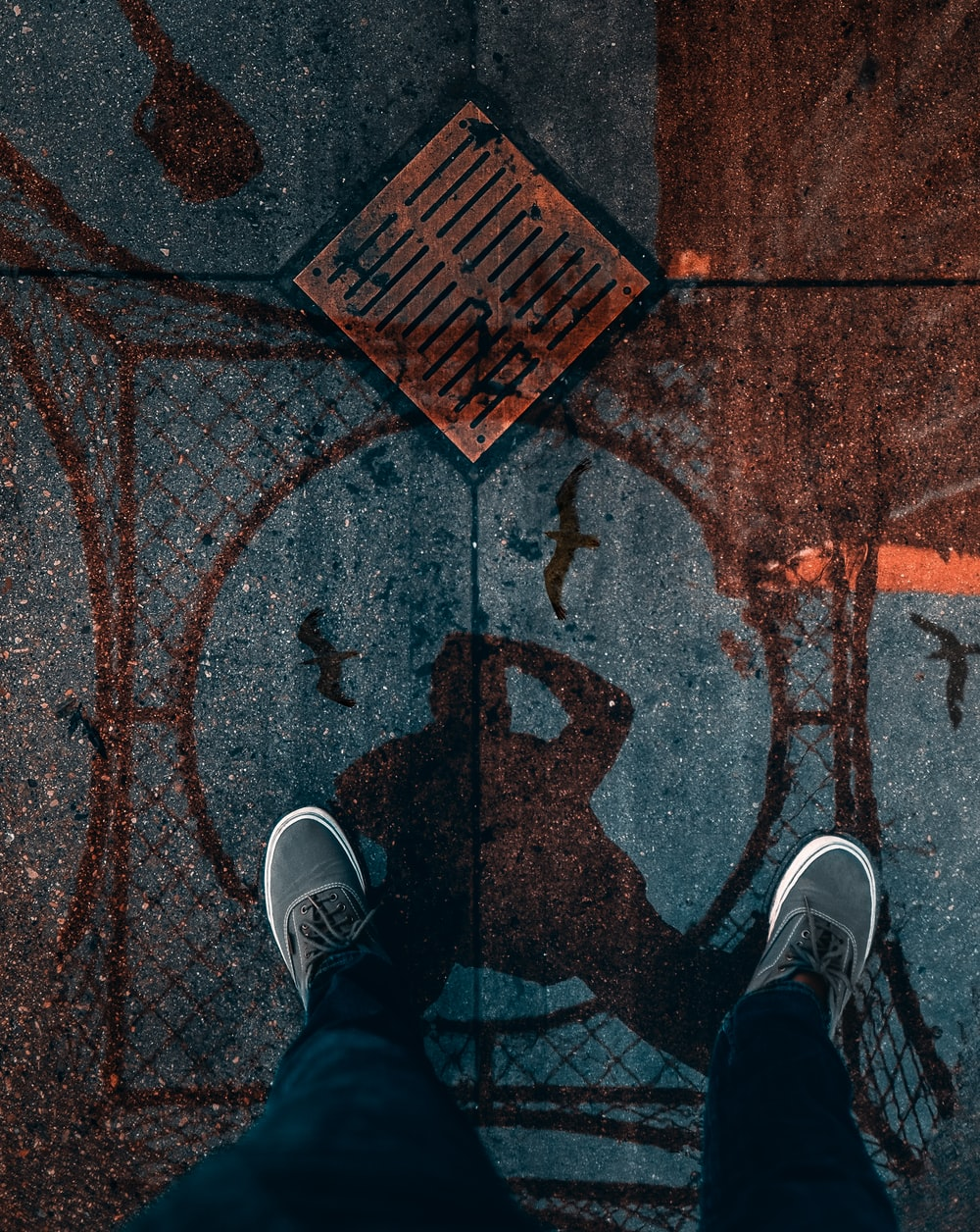 man standing on the street with reflection on water