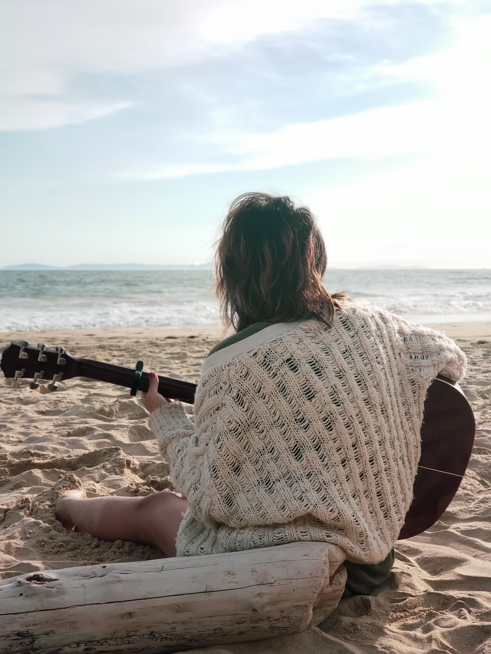 woman sitting on shore holding guitar